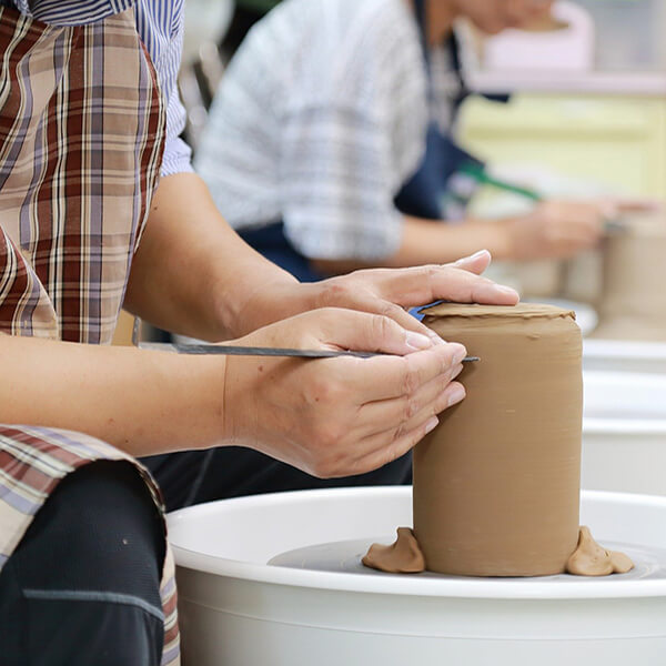 2 people making pottery from clay